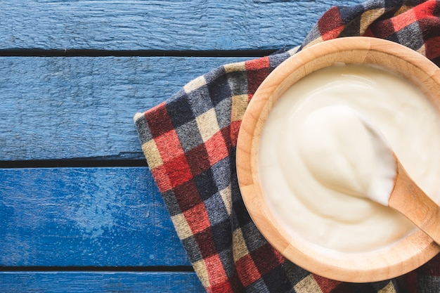 Top view of yogurt in wooden bowl on wooden table
