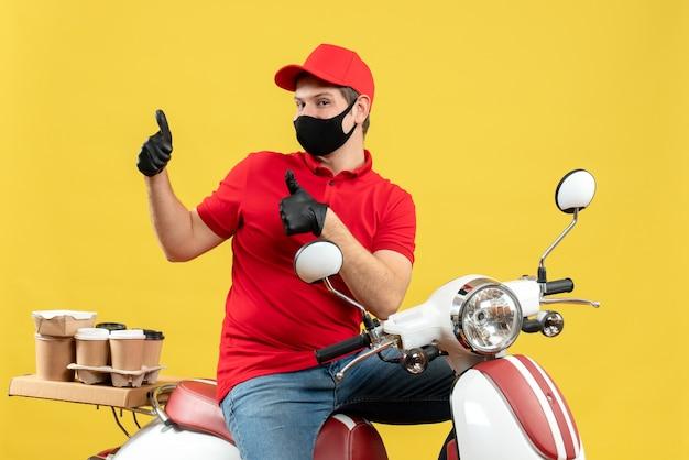 Vista dall'alto del giovane adulto che indossa camicetta rossa e guanti cappello in maschera medica offrendo ordine seduto sullo scooter sentirsi sicuri facendo gesto ok su sfondo giallo