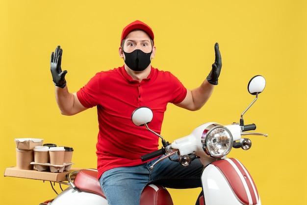 Vista dall'alto del giovane adulto che indossa camicetta rossa e guanti cappello in maschera medica offrendo ordine seduto sullo scooter sensazione scioccata su sfondo giallo