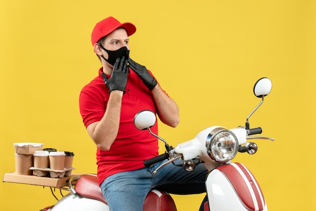 Vista dall'alto del giovane adulto che indossa camicetta rossa e guanti cappello in maschera medica offrendo ordine seduto su scooter focalizzato su qualcosa su sfondo giallo