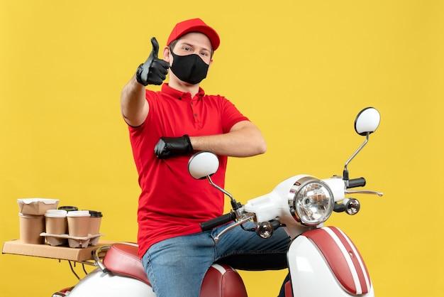 Vista superiore del giovane adulto che indossa la camicetta rossa e guanti cappello nella mascherina medica che trasporta l'ordine che si siede sullo scooter che fa gesto giusto su fondo giallo