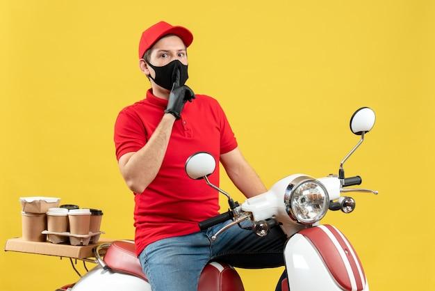 Vista superiore del giovane adulto che indossa la camicetta rossa e guanti del cappello in mascherina medica che trasporta l'ordine che si siede sullo scooter che fa il gesto di silenzio su fondo giallo
