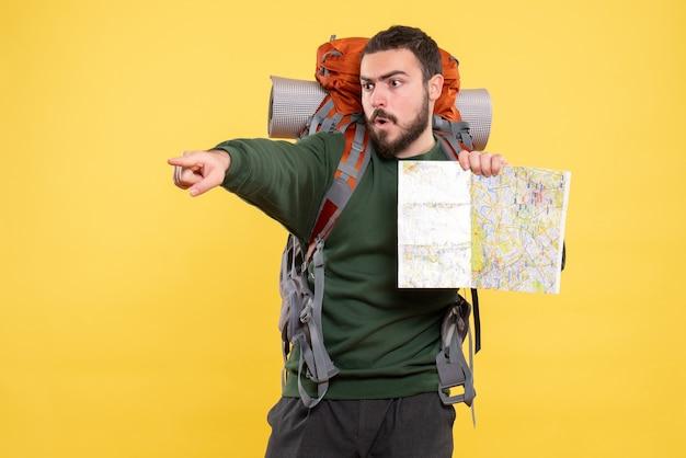 Vista dall'alto di un giovane ragazzo in viaggio arrabbiato con uno zaino che tiene in mano una mappa e punta in avanti sul giallo