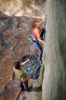 Top view of young athletic girl climber climbing steep natural rock wall.