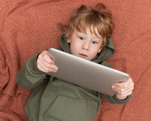 Top view of young boy using tablet in bed
