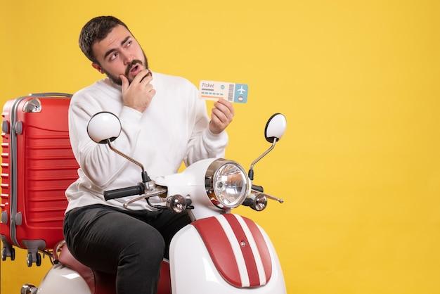 Vista dall'alto di un giovane uomo in viaggio di brainstorming seduto su una motocicletta con la valigia sopra che tiene il biglietto su giallo