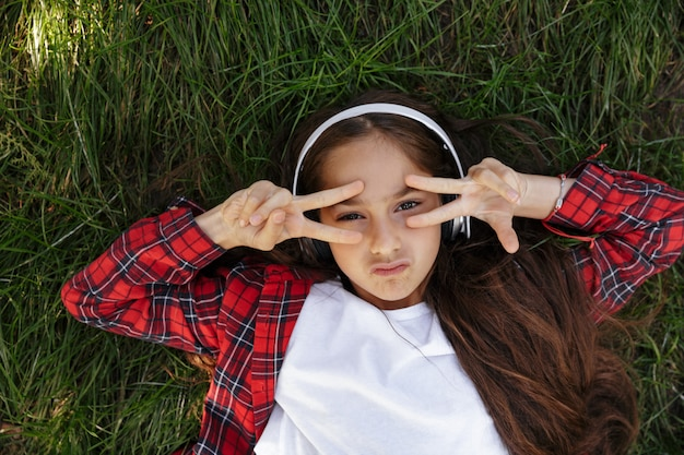 Top view of young brunette girl lying on grass
