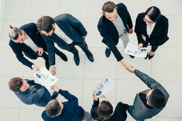 上面図。若いビジネスマンは握手でお互いに挨拶します。