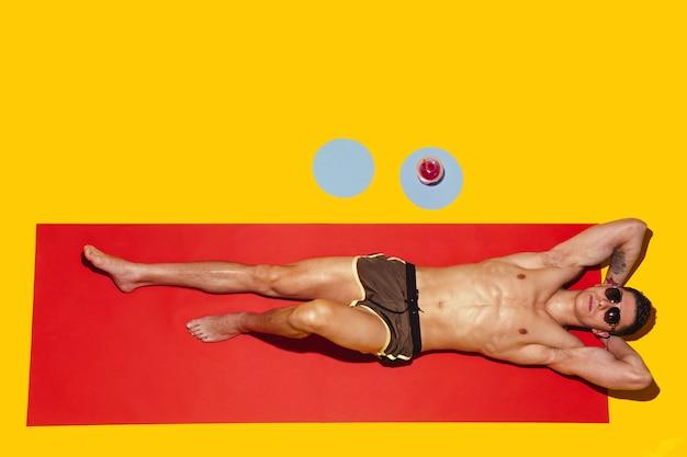 Vista dall'alto del giovane modello maschio caucasico che riposa sulla località balneare sul tappetino rosso e giallo