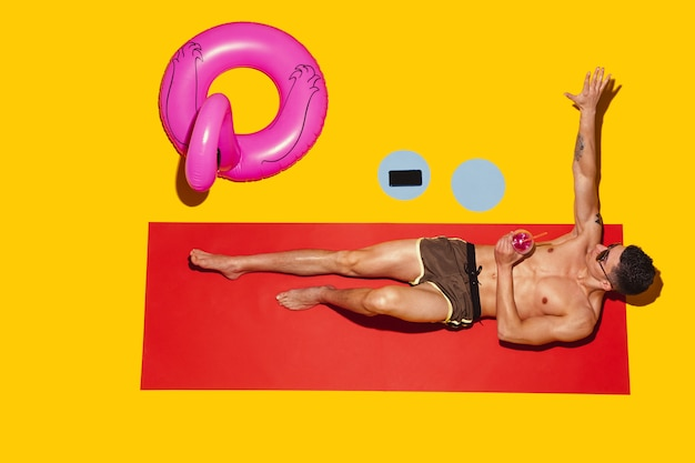 Top view of young caucasian male model's resting on beach resort on red mat and yellow