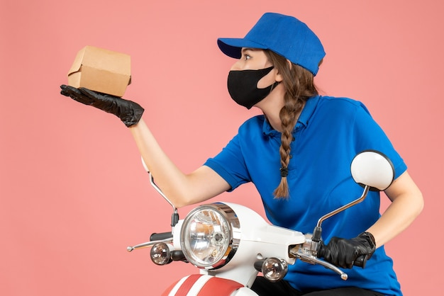 Top view of young concentrated female courier wearing medical mask and gloves holding box on pastel peach
