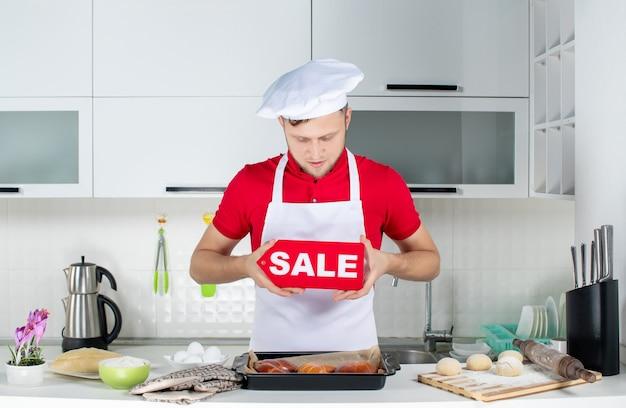 Vista dall'alto di un giovane chef maschio concentrato che mostra il cartello di vendita nella cucina bianca