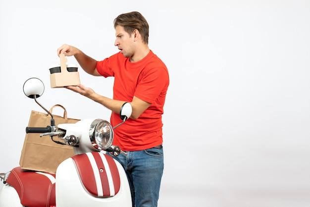 Vista dall'alto di giovane ragazzo di consegna confuso in uniforme rossa in piedi vicino a scooter guardando l'ordine sul muro bianco