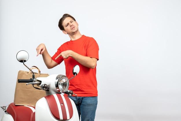Vista dall'alto di giovane ragazzo di consegna confuso in uniforme rossa in piedi vicino a scooter sul muro bianco