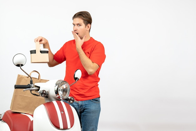 Vista dall'alto di giovane ragazzo di consegna confuso ed emotivo in uniforme rossa in piedi vicino a scooter che mostra ordine sul muro bianco