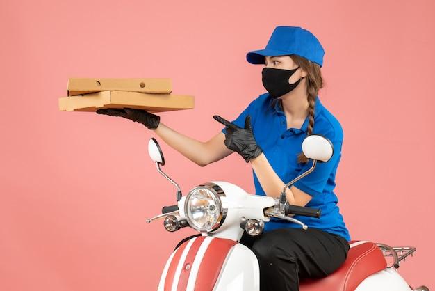 Vista dall'alto del giovane corriere femminile confuso che indossa maschera medica e guanti seduto su uno scooter che consegna ordini su pesca pastello