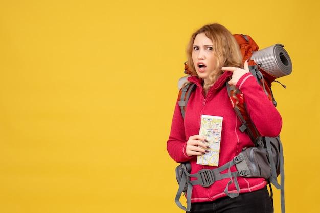 Vista dall'alto di giovane ragazza in viaggio confusa in mascherina medica raccogliendo i suoi bagagli e tenendo la mappa