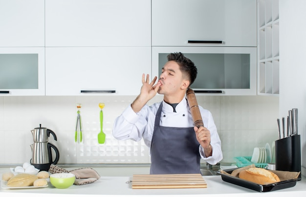 Top view of young cook in uniform standing behind the table holding grater and making perfect gesture in the white kitchen