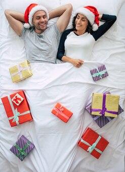ベッドに座っているサンタの帽子のトップビュー若いカップル