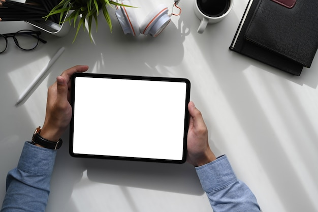 Top view of a young creative graphic designer hands holding digital tablet on white table.