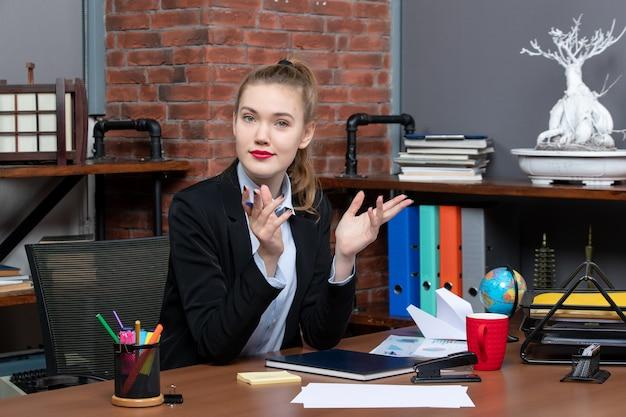 Vista dall'alto di una giovane curiosa impiegata seduta alla sua scrivania e in posa per la macchina fotografica