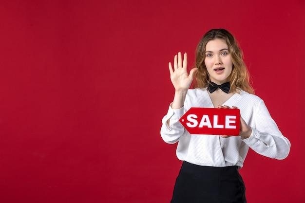 Vista dall'alto di una giovane donna curiosa con papillon sul collo e con cartello di vendita che mostra cinque sulla parete rossa
