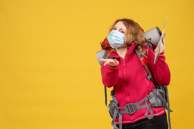Vista dall'alto di giovane ragazza in viaggio curiosa in mascherina medica raccogliendo i suoi bagagli e tenendo la mappa