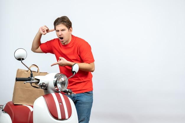 Vista dall'alto di giovane ragazzo delle consegne in uniforme rossa in piedi vicino a scooter e ha perso la testa sul muro bianco
