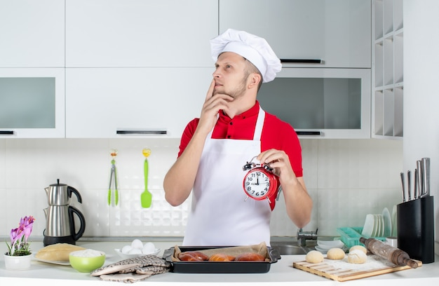 Top view of young dreamy male chef holding clock in the white kitchen