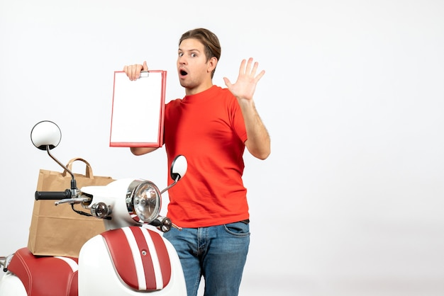 Top view of young emotional confused delivery guy in red uniform standing near scooter showing document on white wall