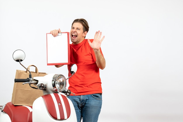 Top view of young emotional nervous delivery guy in red uniform standing near scooter showing document on white wall