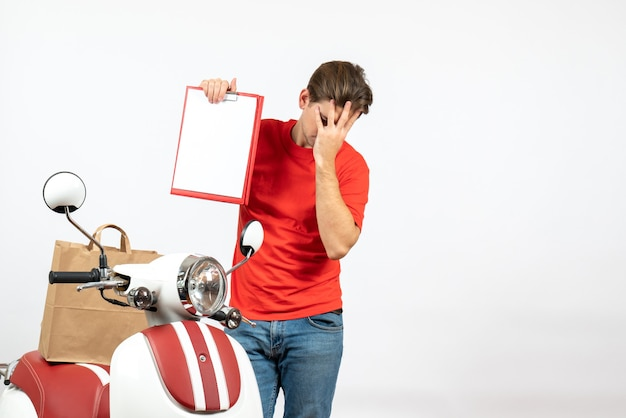 Top view of young emotional overtired delivery guy in red uniform standing near scooter showing document on white wall