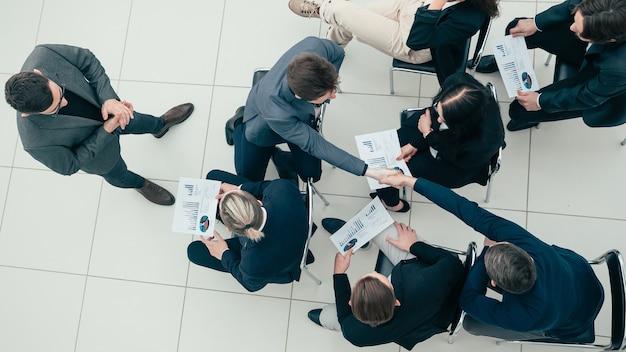 上面図。握手で支え合う若い社員たち。