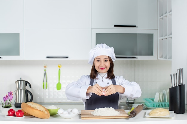 Top view of young female chef in uniform standing behind table breaking egg into food in the white kitchen