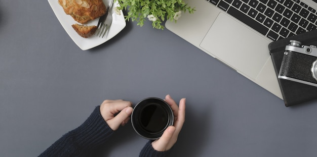 Top view of young female holding coffee cup in winter workspace with office supplies on grey desk