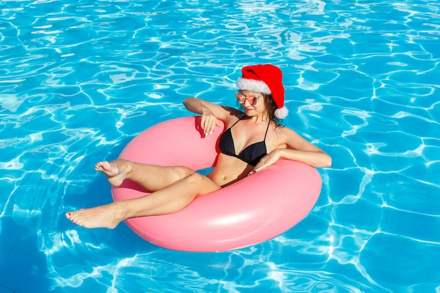 Top view of young female in santa claus hat swim with pink circle in pool