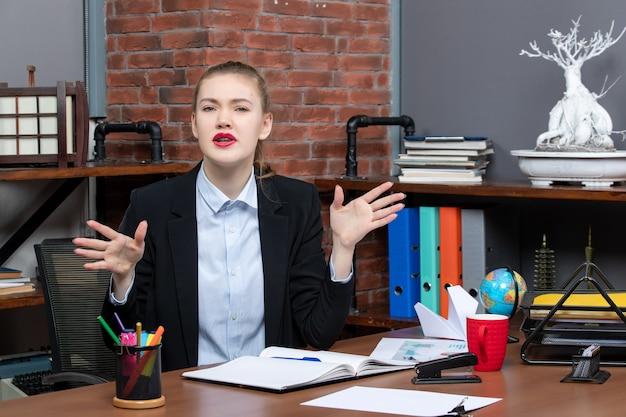 Vista dall'alto di una giovane donna seduta a un tavolo e nervosa in ufficio