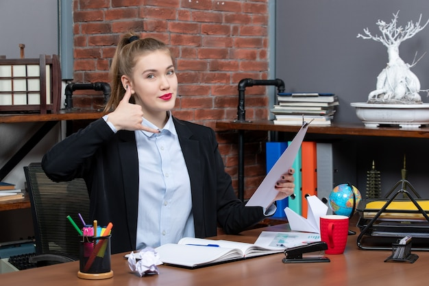 Top view of young female sitting at a table and holding the document making call me gesture in the office
