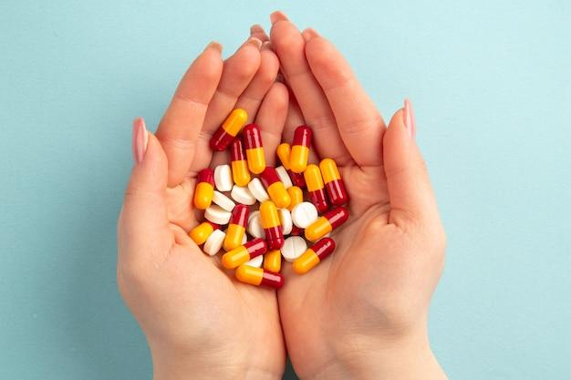 上面図青い背景の上の彼女の手に丸薬を持つ若い女性パンデミックcovid-ウイルス健康研究所科学病院の色