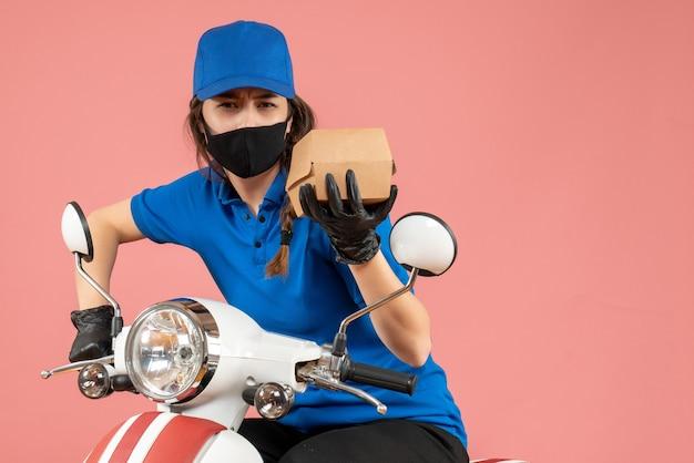 Vista dall'alto del giovane corriere femminile focalizzato che indossa maschera medica e guanti che tengono scatola su pesca pastello