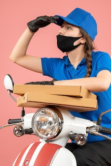 Vista dall'alto del giovane corriere femminile focalizzato che indossa maschera medica e guanti che tengono scatole su pesca pastello pastel