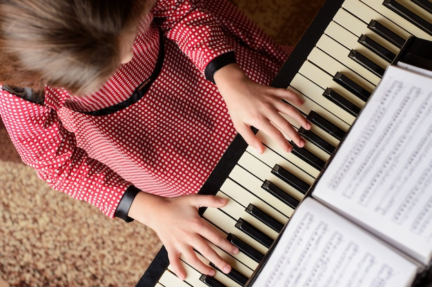 Top view of a young girl playing the piano at home