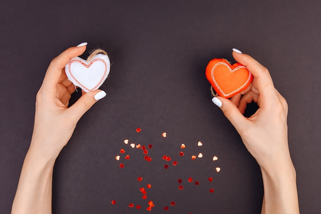 Top view of young girl's hands are holding red and white hearts. around candy from red hearts. grey background. valentine's day.
