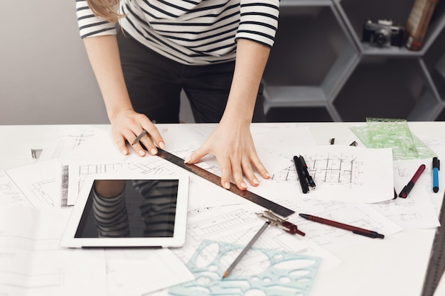 Top view of young good-looking architect student girl in casual striped shirt and black jeans standing near table, holding ruler and pen in hands making drawings, watching movie on digital table, gett