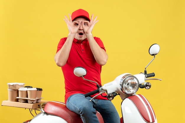 Top view of young guy wearing red blouse and hat delivering orders making eyegasses gesture on yellow background
