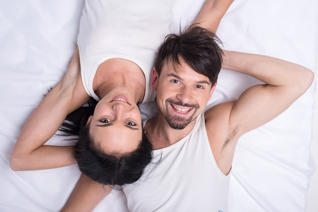 Top view of a young happy couple in bed.