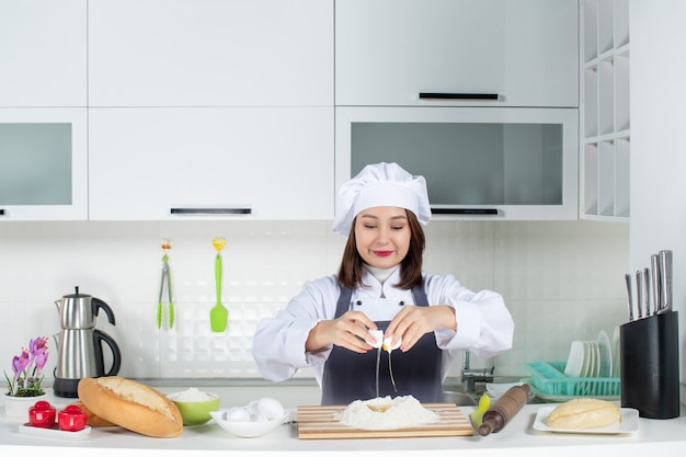 Vista dall'alto di una giovane chef donna felice in uniforme in piedi dietro il tavolo che rompe l'uovo nel cibo nella cucina bianca