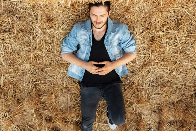 Top view of young man in denim jacket lying on dry hay in the field.