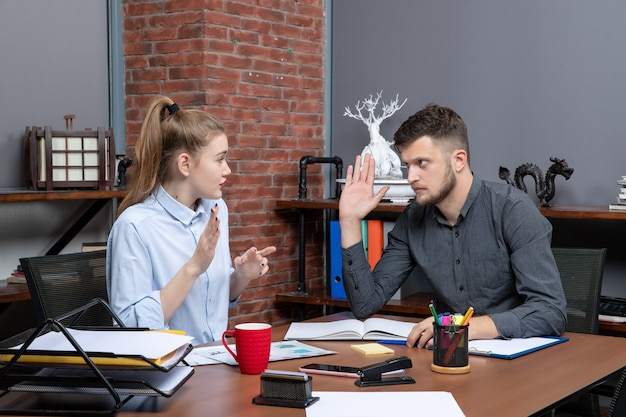 Top view of young man and female co-worker discussing one issue in office enviroment