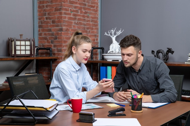 Top view of young man and his female co-worker sitting at the table discussing one issue in office enviroment